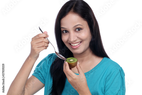 Happy woman holding kiwi and teaspoon