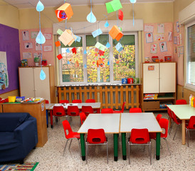 classroom in a kindergarten with tables and red chairs