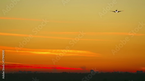 Boeing 737 jet airliner approaching airport at dawn.