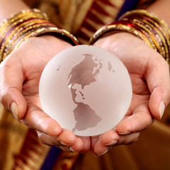 Traditional woman hands holding a glass globe