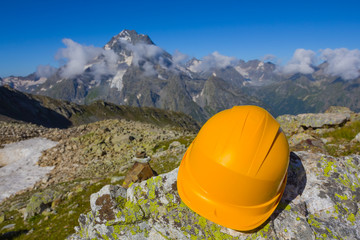 yellow helmet on a stone in a mountains