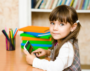 little girl using tablet computer. looking at camera