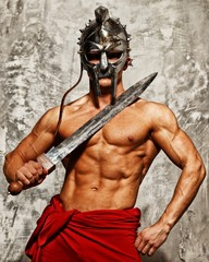 Gladiator with muscular body with sword and helmet