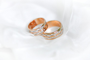 Two wedding gold wedding rings are on a background a white veil