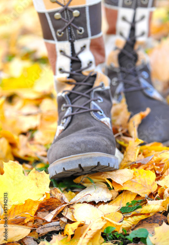 Woman walking on a street with autumn leaves