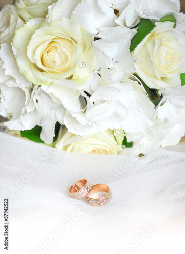 Gold wedding rings on a white veil and wedding roses bouquet