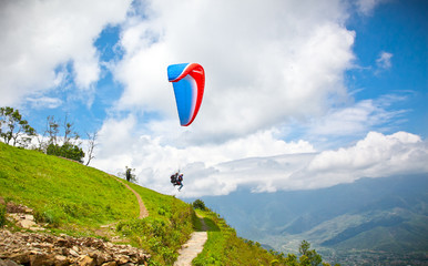 Paraglider flying against the Himalayas, Nepal.