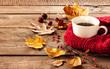 Leinwandbild Motiv Hot coffee and autumn leaves on vintage wood background