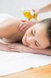 Beautiful woman enjoying oil massage at beauty spa