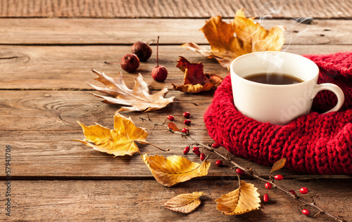 canvas print picture Hot coffee and autumn leaves on vintage wood background