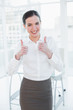 Elegant businesswoman gesturing thumbs up in office