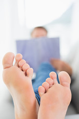 Blurred man reading a book with focus on bare feet