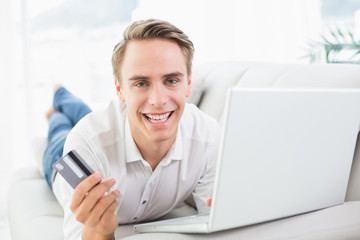 Cheerful man doing online shopping on sofa at home