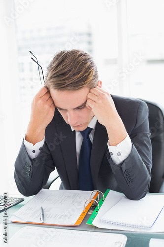 Worried businessman looking at documents in office