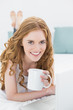 Smiling blond with coffee cup using laptop in bed