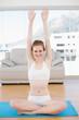 Sporty woman raising hands in fitness studio