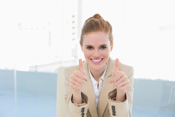 Elegant businesswoman gesturing thumbs up