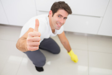 Man cleaning the kitchen floor while gesturing thumbs up