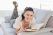 Portrait of casual woman reading a book on sofa