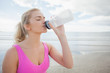 Beautiful healthy woman drinking water on beach