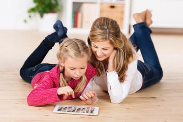 mutter und tochter schauen fotos am tablet-pc