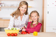 mutter und kind schneiden gemüse für salat