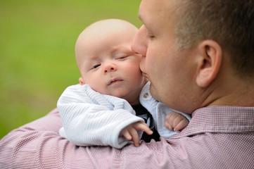 Glücklicher Vater hält sein Baby auf dem Arm