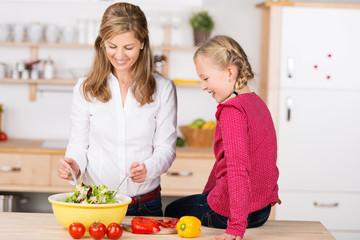 tochter schaut ihrer mutter beim salat machen zu