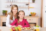 mutter und tochter mit gesundem obst in der küche