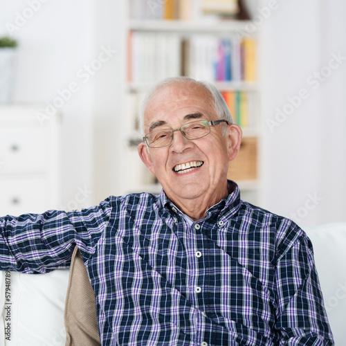 lächelnder senior sitzt entspannt zu hause