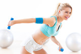 Fototapety Woman in gym exercising with dumbbells