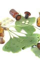 Ginkgoblätter mit Globuli und Tabletten