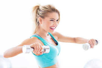 Woman in gym exercising with dumbbells