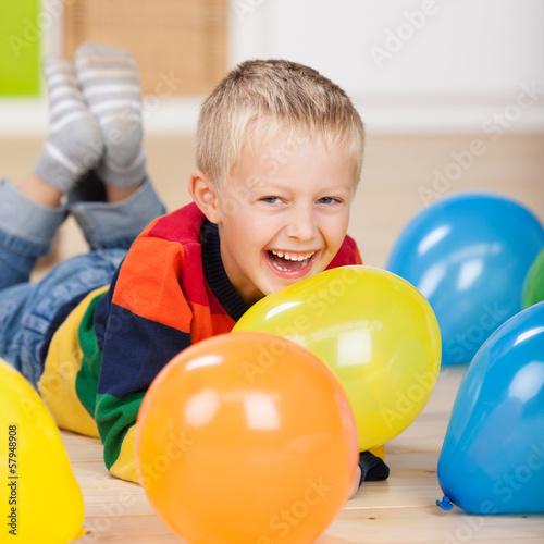 lachender kleiner junge mit luftballons