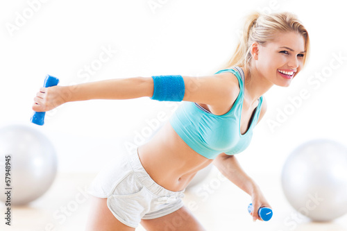 Woman in gym exercising with dumbbells - 57948945