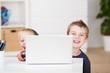 zwei lachende kinder schauen hinter laptop hervor