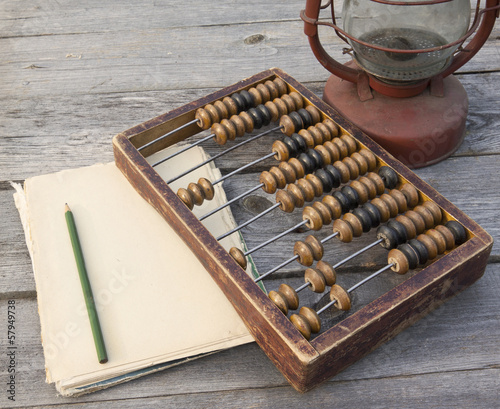 Old abacus, the paper with a pencil next to  lamp
