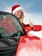 Miss Santa driving a red roadstar, shows thumb up