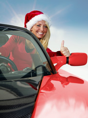 Miss Santa driving a red roadstar, shows thumb up
