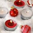 rote und weiße Teelichter im Schnee