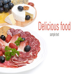 assorted deli meats and a plate of cheese and grapes, isolated