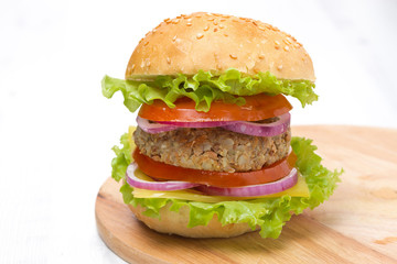 Burger with a vegetarian cutlet and fresh vegetables on board
