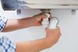 Plumber's hands and washbasin drain at bathroom