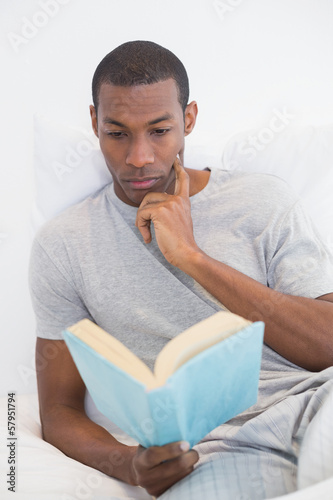 Relaxed Afro man reading book in bed