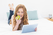Casual blond using tablet PC while eating apple in bed