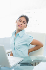 Young businesswoman suffering from back ache in office