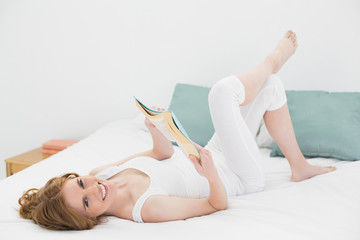 Portrait of relaxed woman reading a book in bed