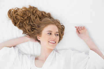 Overhead view of a smiling young blond in bed