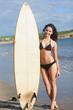 Full length of bikini woman holding surfboard at beach
