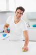 Portrait of a smiling man cleaning kitchen counter